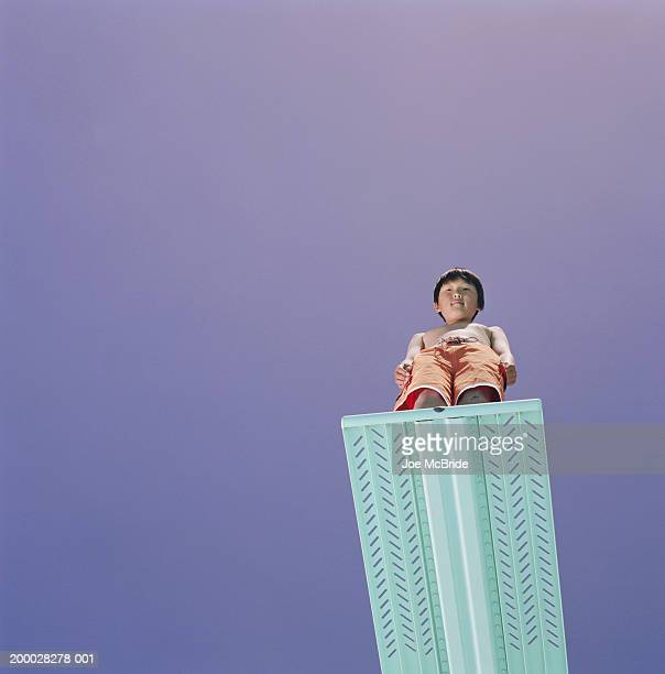 Boy (9-11) standing on edge of diving board, looking down, low angle