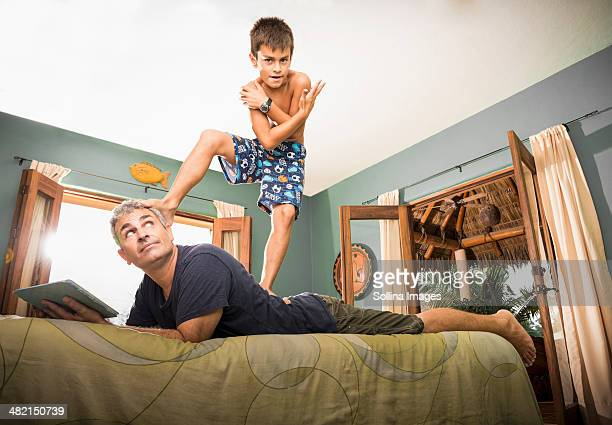 Boy standing on father on bed