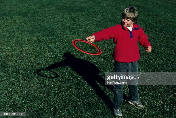 Boy (6-7) standing on grass with ring frisbee, elevated view