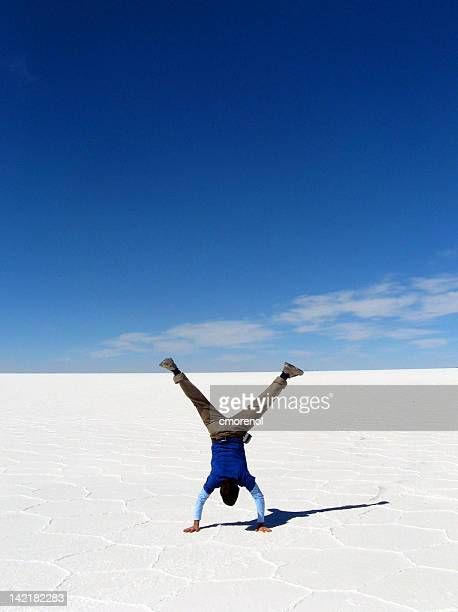 Boy standing on his hands on sand