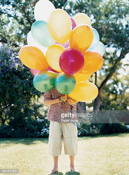 boy standing on lawn behind a bunch of balloons obscuring his face - large group of objects stock pictures, royalty-free photos & images