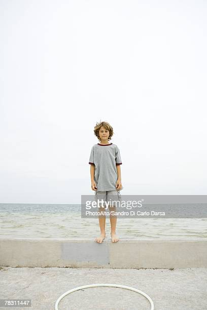 boy standing on low wall at the beach, looking at camera - shorts stock pictures, royalty-free photos & images