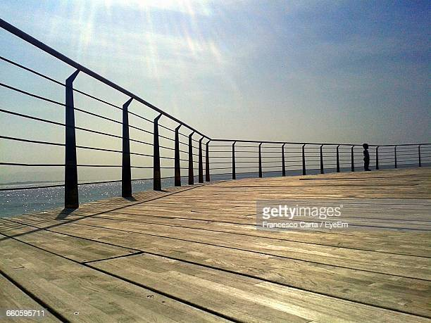 Boy Standing On Pier By Sea Against Sky