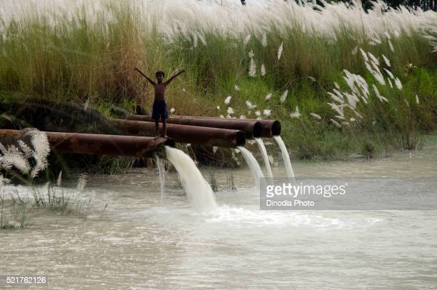 Boy standing on pipeline falling in pond, Kolkata, West Bengal, India, Asia