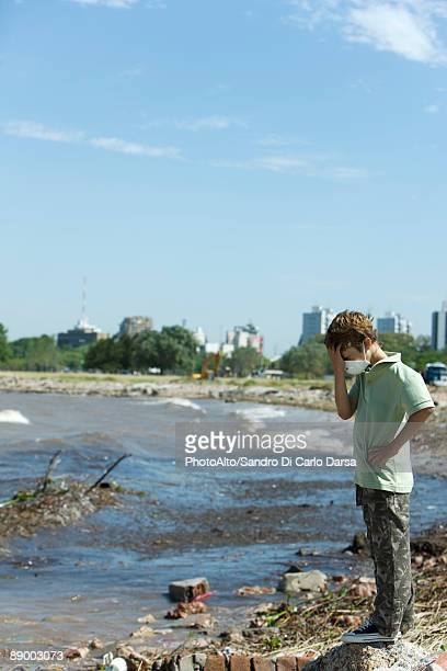 boy standing on polluted shore, wearing pollution mask, head down - 水質汚染 ストックフォトと画像