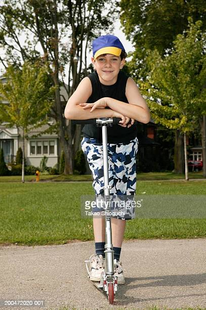 Boy (9-11) standing on push scooter, portrait