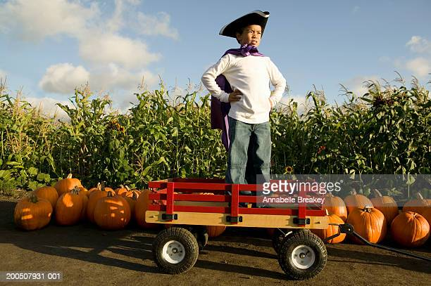 boy (6-8) standing on red wagon in cape and hat - toy wagon stock photos and pictures