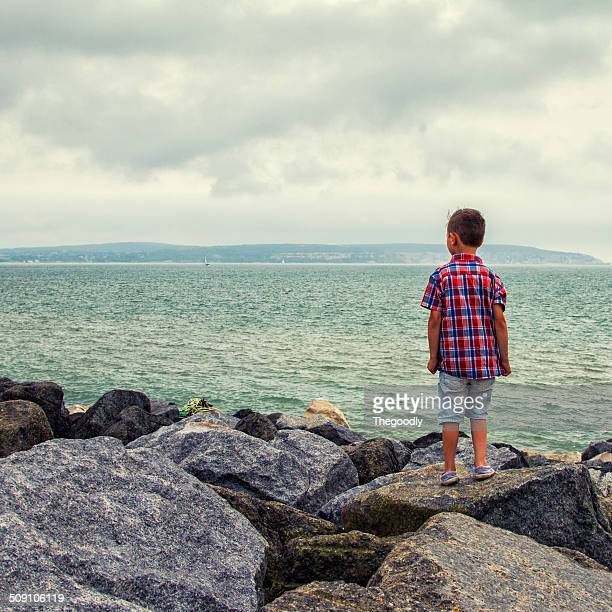 Boy standing on rocks looking at sea
