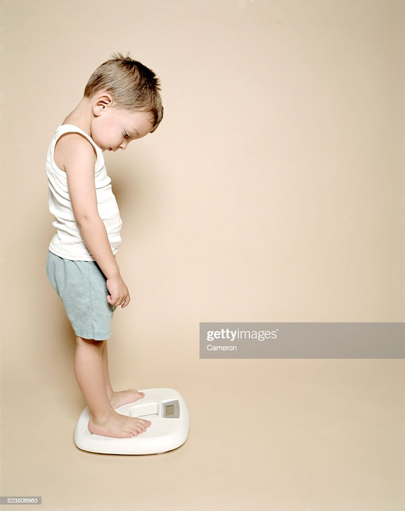 Boy Standing on Scale : Stock Photo
