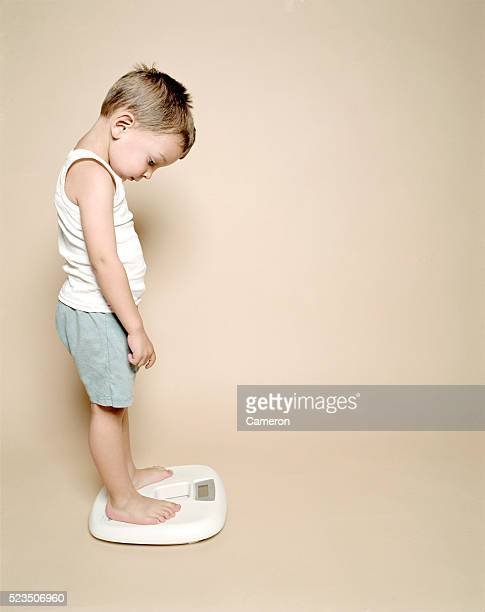 boy standing on scale - cameron young stock photos and pictures