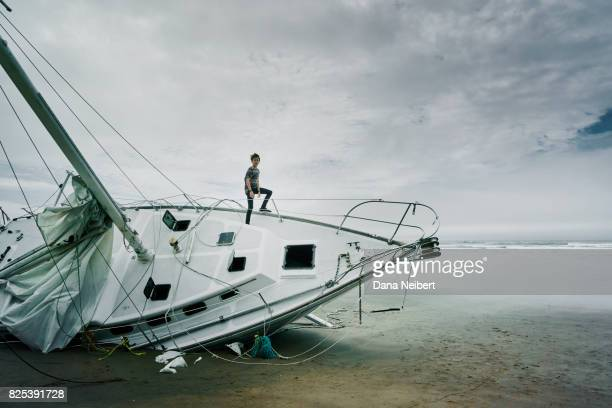 Boy standing on shipwrecked sailboat on the beach