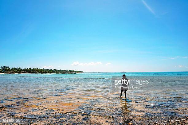 Boy Standing On Shore Against Blue Sky
