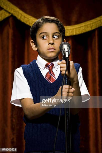 boy standing on stage with microphone and big eyes - big mike stock pictures, royalty-free photos & images