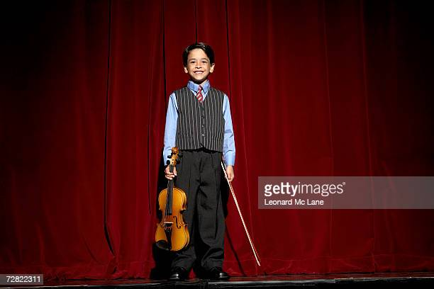 Boy (6-7) standing on stage with violin