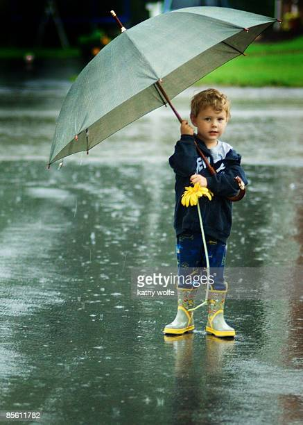 boy standing on street holding umbrella - kathy shower stock pictures, royalty-free photos & images