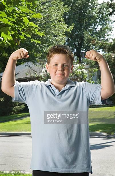 Boy (8-10) standing on suburban driveway, flexing muscles, portrait