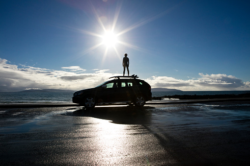 Boy standing on surf board on top of a car, looking out to sea - gettyimageskorea