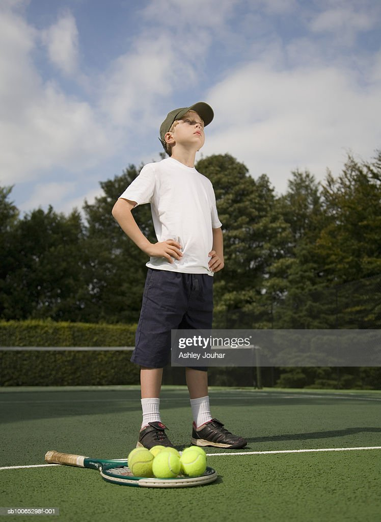 Boy (6-7) standing on tennis court next to racket and balls : Foto stock