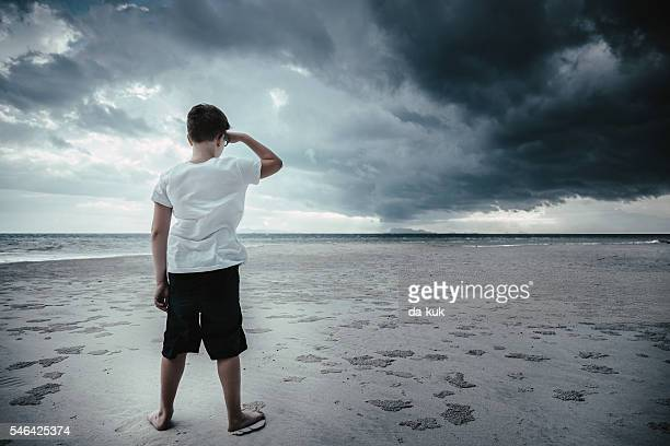 Boy standing on the beach and looking forward