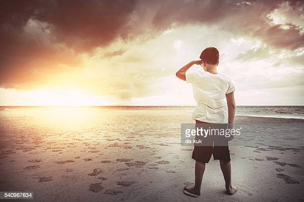 Boy standing on the beach at sunset and looking forward