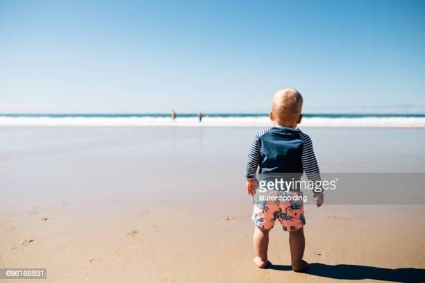 Boy standing on the beach, Noosa Heads, Queensland, Australia
