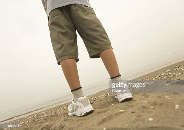 boy standing on the beach - bermuda shorts stock pictures, royalty-free photos & images