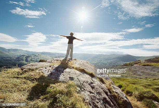 boy (8-9) standing on top of rock with arms outstretched - hill stock pictures, royalty-free photos & images