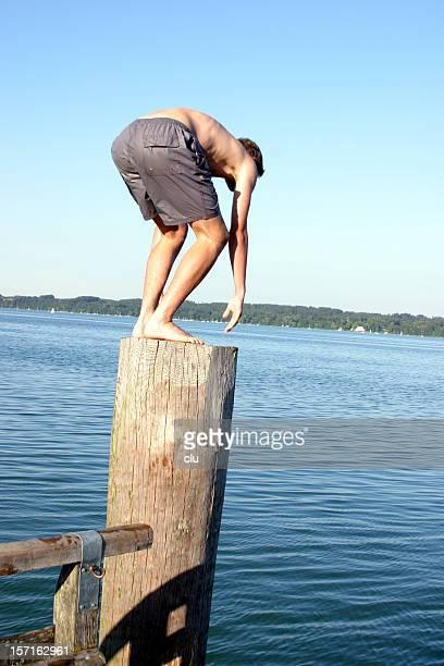 Niño parado en la columna corta madera antes de saltar al lago