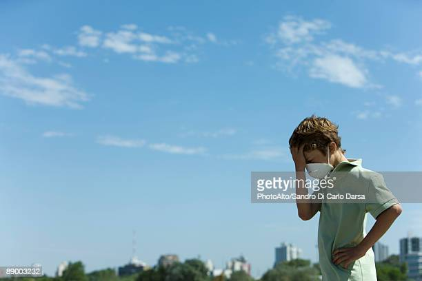 Boy standing outdoors wearing pollution mask, holding head, city in background