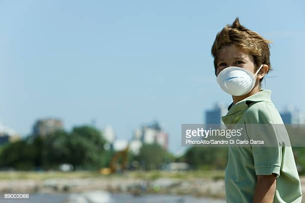 Boy standing outdoors, wearing pollution mask