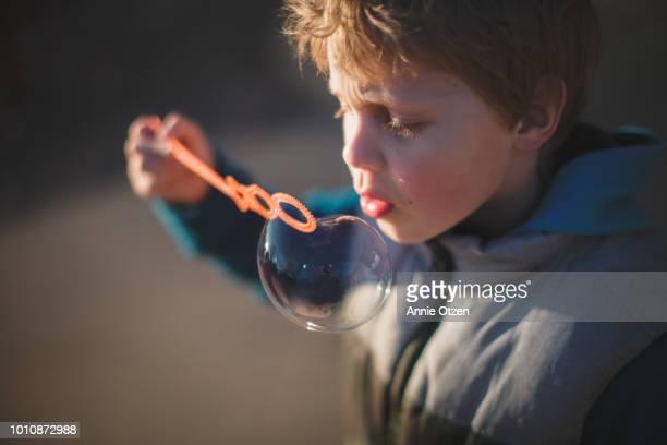 Boy standing outside blowing bubbles