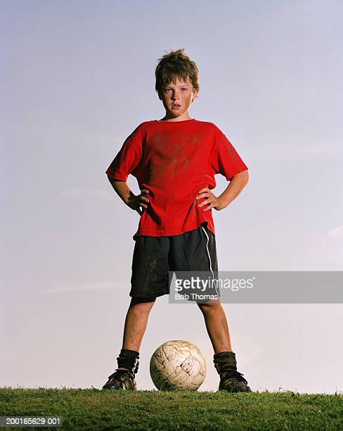 Boy (10-12) standing over football, portrait