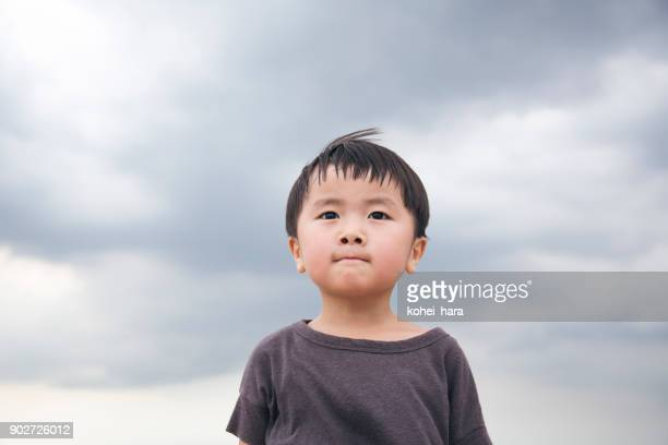 boy standing under a cloudy sky - independence stock pictures, royalty-free photos & images