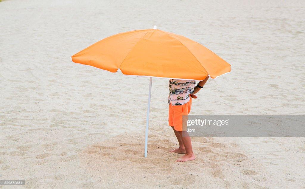 Boy standing under beach umbrella : Stock Photo