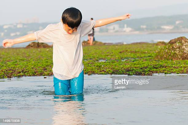 Boy standing up from water at seacoast