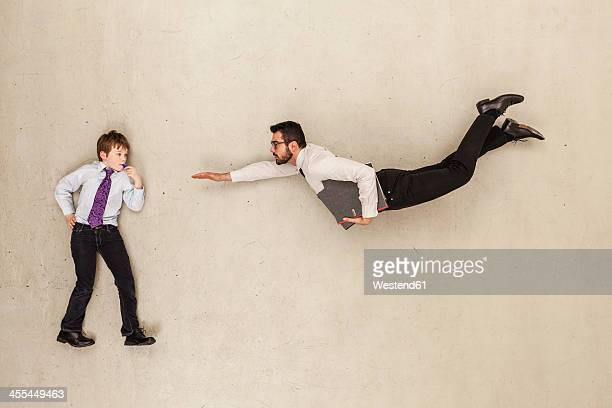 Boy standing while businessman flying