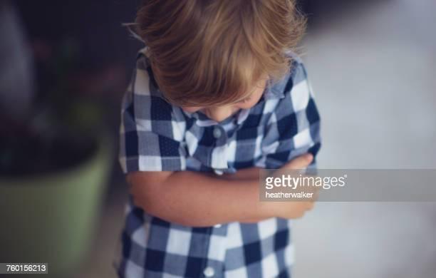 boy standing with arms crossed - peuter stockfoto's en -beelden