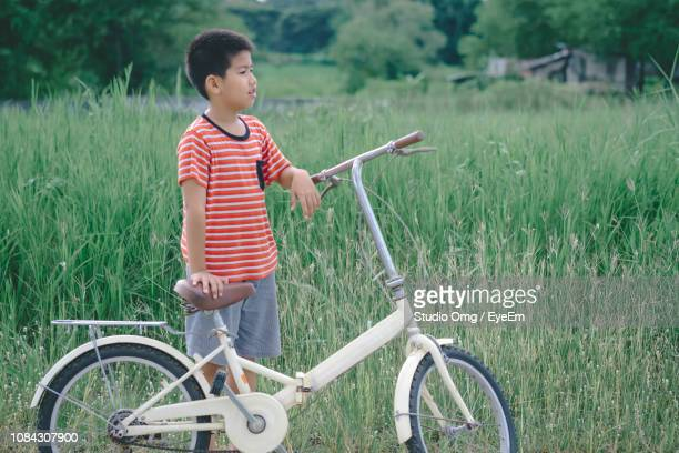 Boy Standing With Bicycle On Field