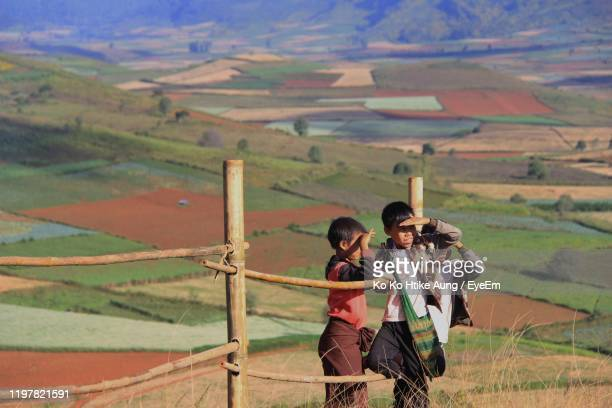 boy standing with brother against landscape - ko ko htike aung stock pictures, royalty-free photos & images