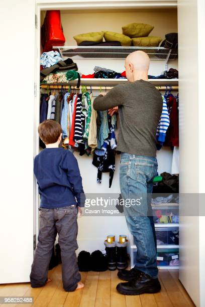 boy standing with father removing clothes from wardrobe - remove clothes from stock pictures, royalty-free photos & images