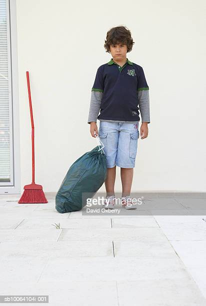 Boy (8-9) standing with garbage bag outside house, portrait