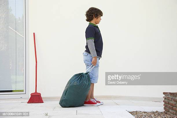 Boy (8-9) standing with garbage bag outside house, side view