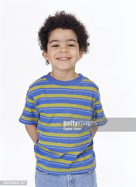 boy (4-6) standing with hands behind back, smiling, portrait - 6 7 anos - fotografias e filmes do acervo