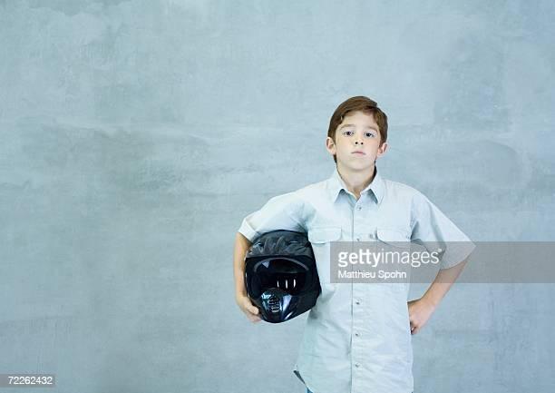 Boy standing with helmet under arm