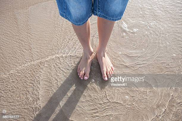 Boy standing with his feet in the sea