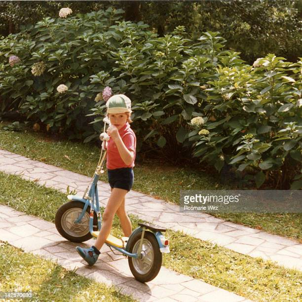 Boy standing with his new scooter in garden