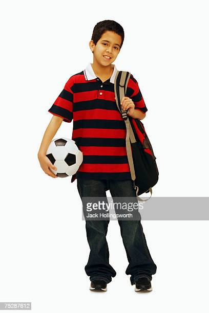 Boy (11-12) standing with soccer ball, portrait