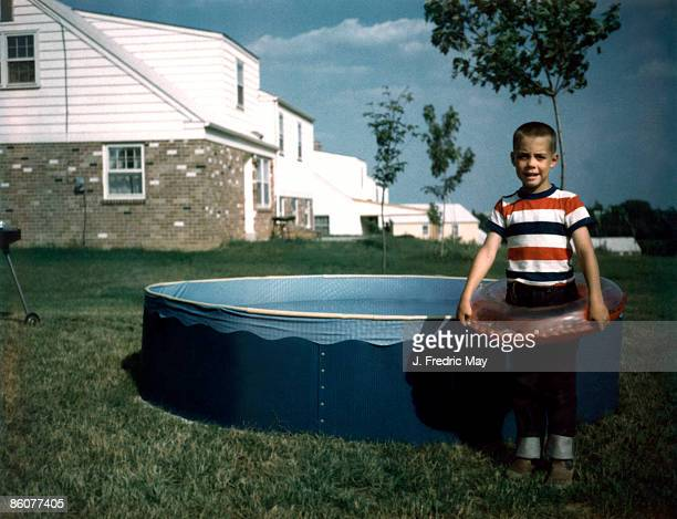 Boy standing with wading pool