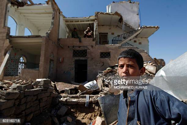 A boy stands amidst the rubble outside a house destroyed by Saudiled coalition air strikes two days earlier on the outskirts of the Yemeni capital...