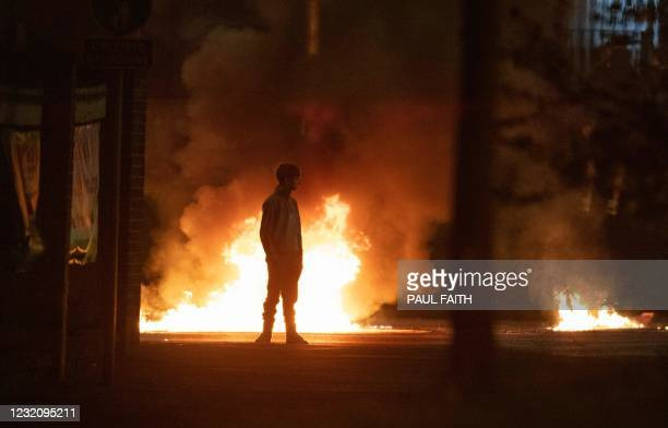 Boy stands and looks on as flames and smoke rises behind him at the scene of violence in Newtownabbey, north of Belfast, in Northern Ireland on April...
